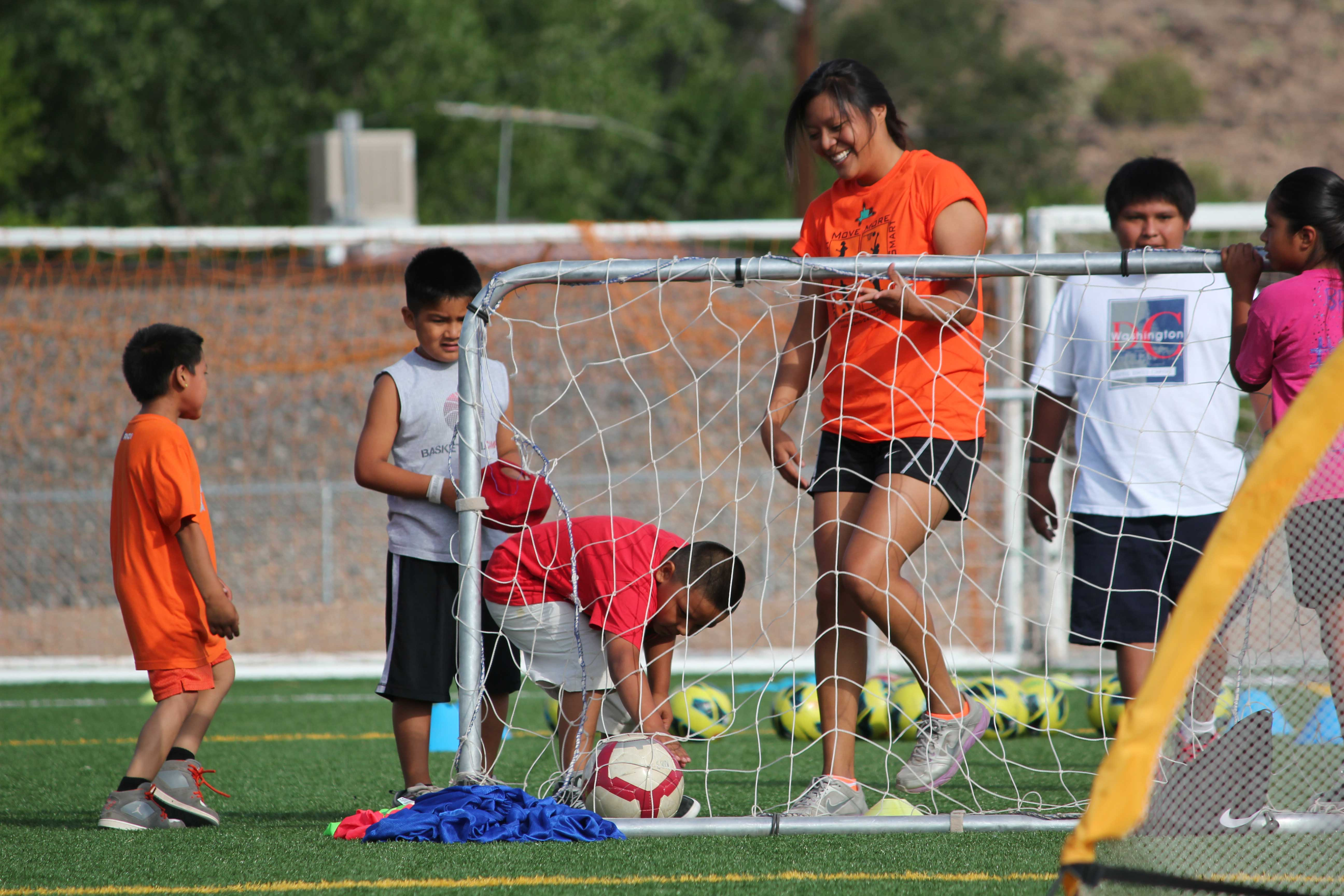 kids playing soccer with coach